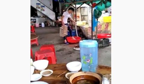 大排档店员用脚洗菜 顾客正在旁边吃饭